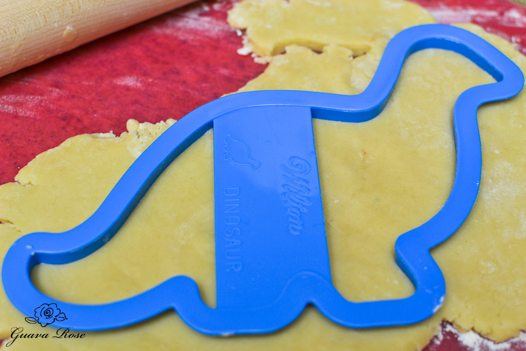 Blue dinosaur cookie cutter in dough
