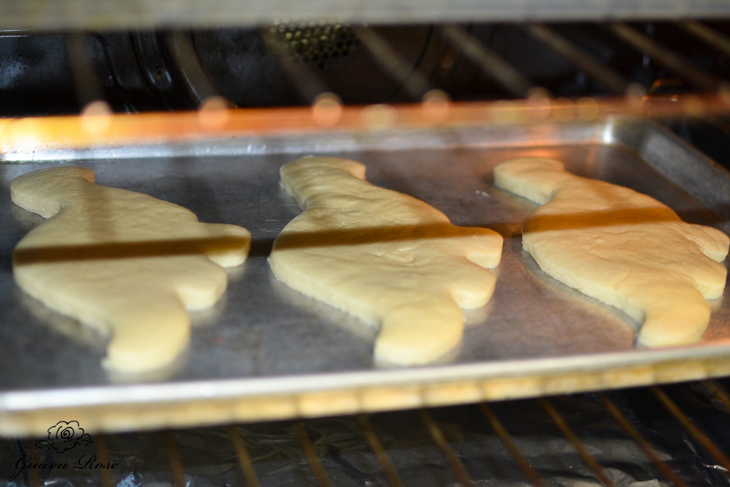 Blue dinosaur cookies baking in oven