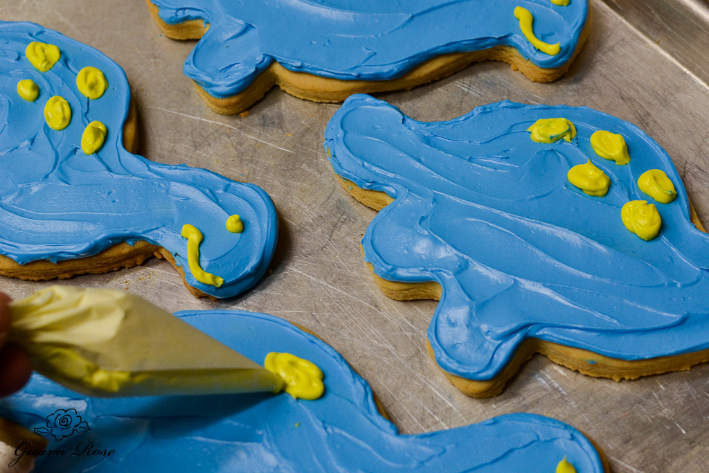 Piping yellow spots on blue dinosaur cookie
