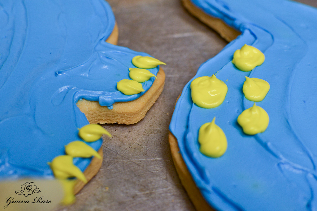 Blue dinosaur cookie, closeup of toenails and spots