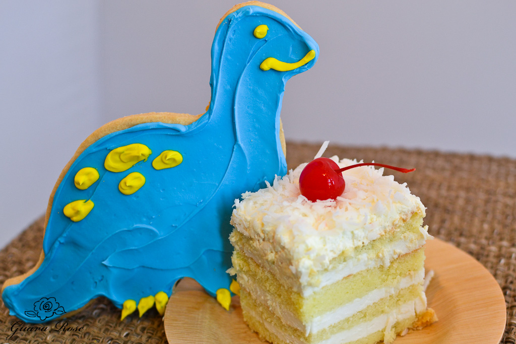 Blue dinosaur cookie nest to a piece of haupia chiffon torte