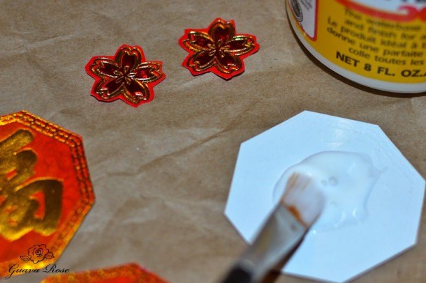 Gluing decorations on chinese candy holder