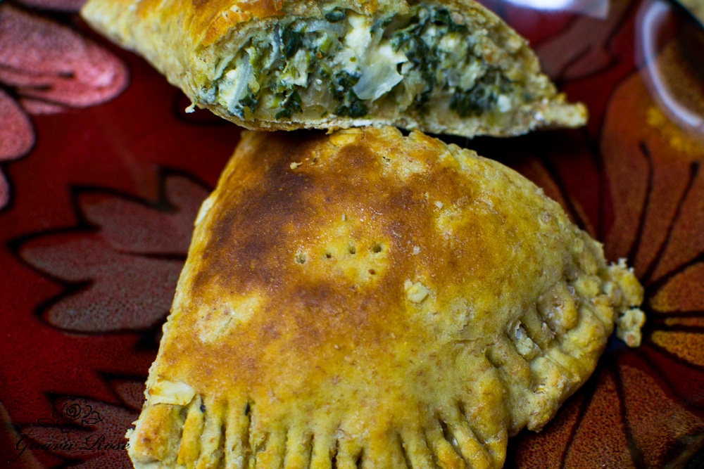 spinach feta pie, half moon shape cut in half on plate