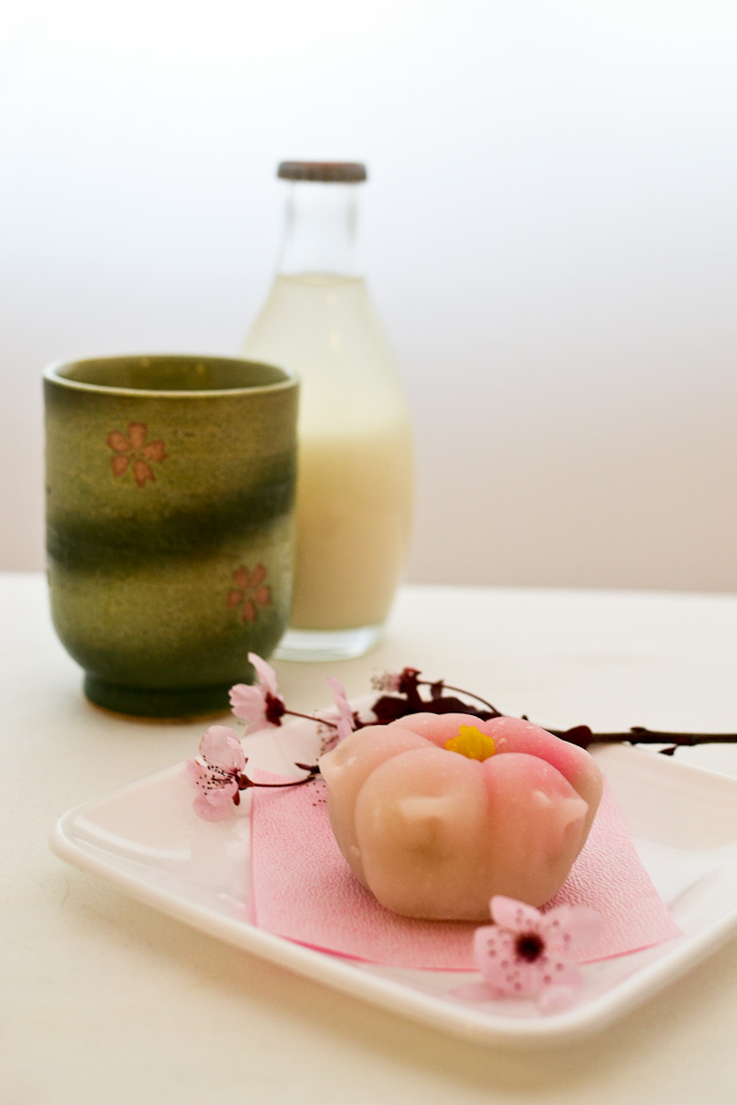 Sakura shaped mochi, bottle of rice wine, tea cup