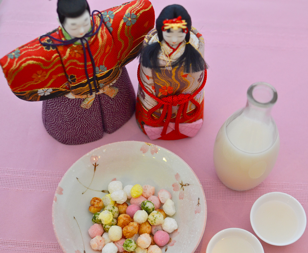 Hinamatsuri dolls with rice wine bottle and cups, rice crackers