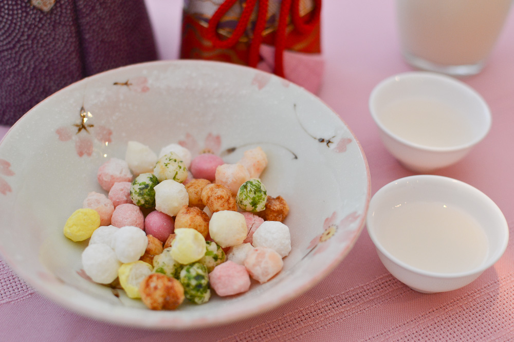 Close up bowl of rice crackers and cups of rice wine for Girl's day