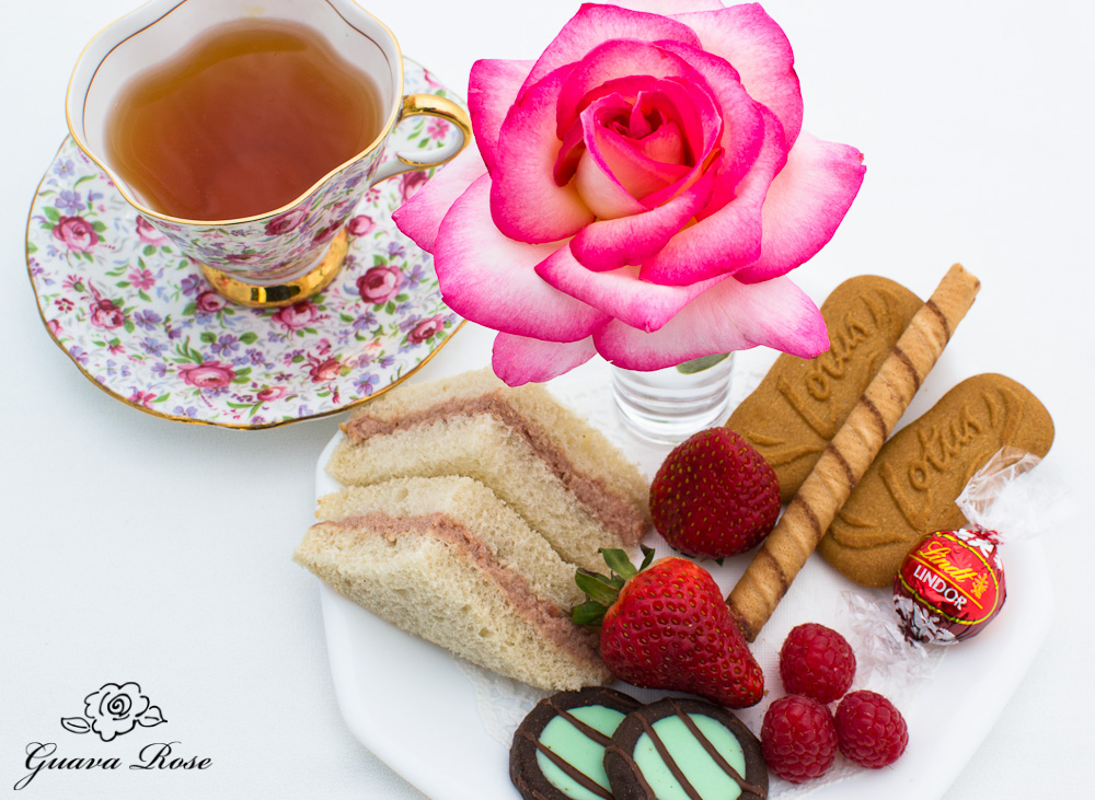 Afternoon tea plate with deviled meat tea sandwiches, full teacup view
