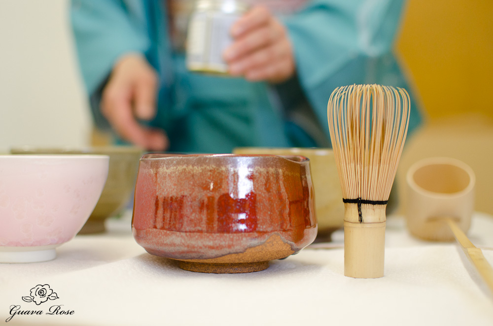 Tea bowls, whisk,ladle, and holding can of matcha in background