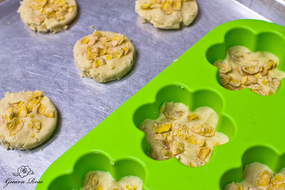 Baking sheet with round cornflake cookies and slicone mold flower cookies
