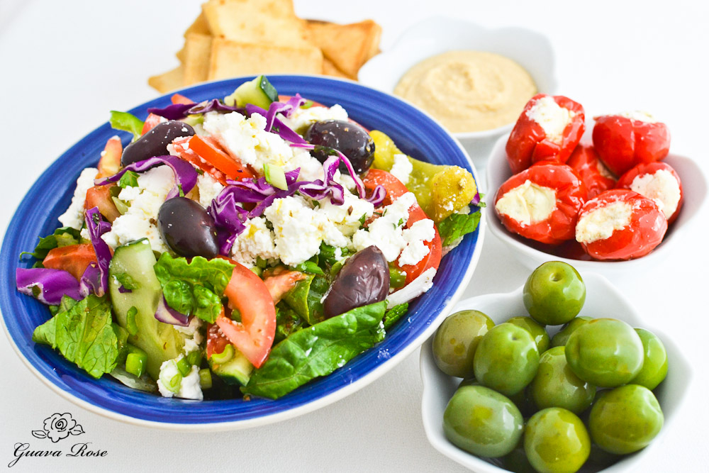 Greek Salad, Hummus and pita chips, stuffed African Peppers, Italian Olives, angled view