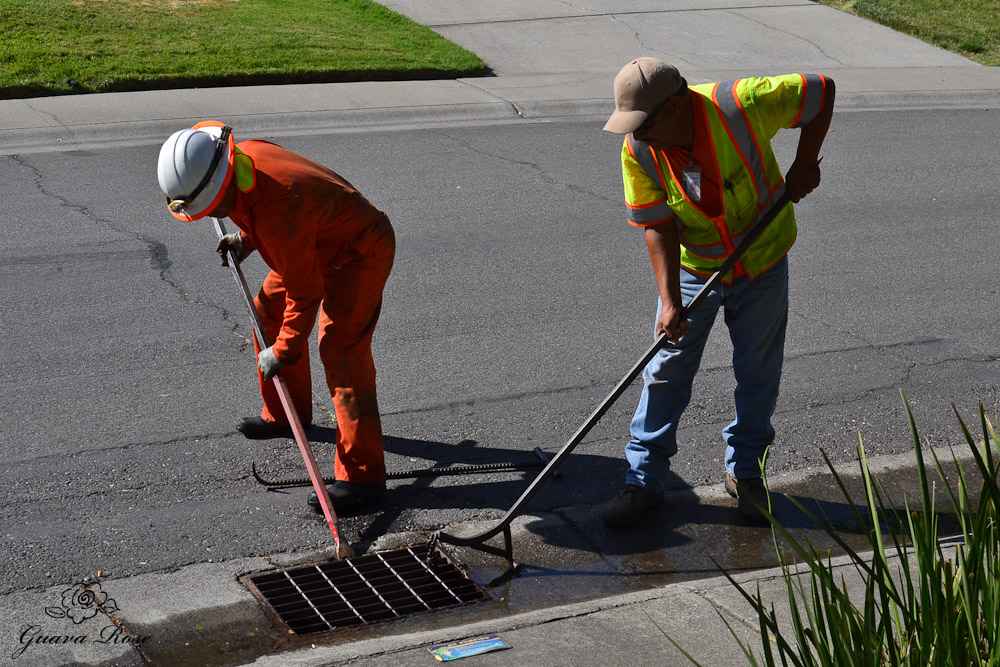 City workers working of loosening drain grate