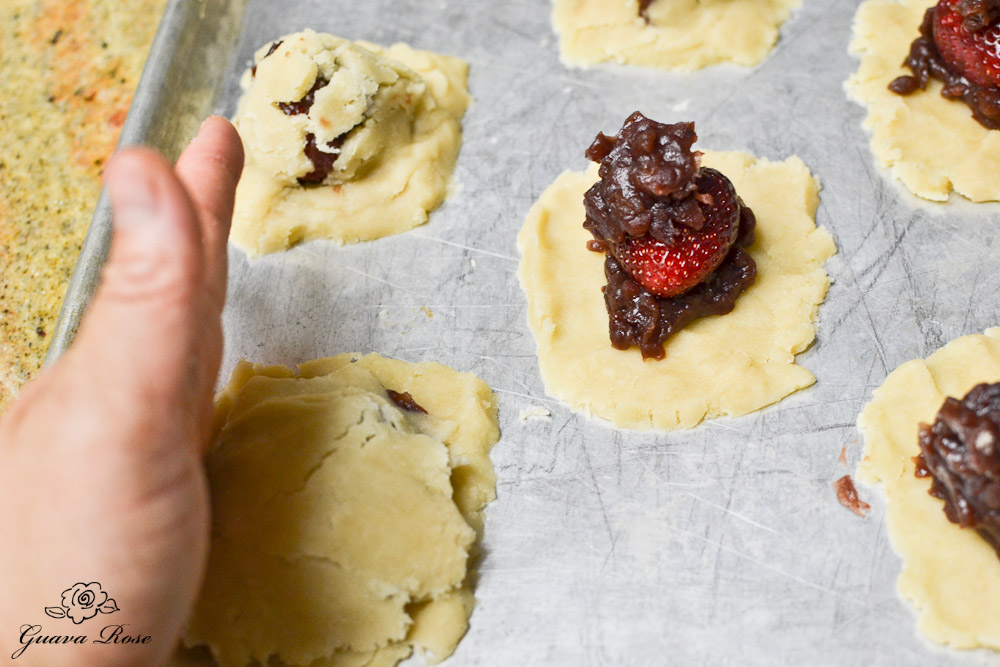 Top dough placed over sweet ban covered strawberry