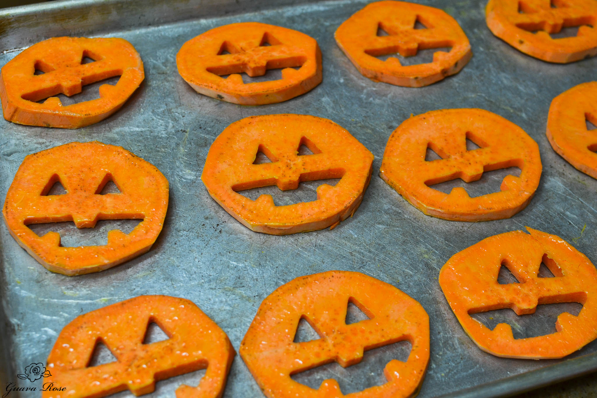 Raw sweet potato jack-o-lanterns on greased sheet
