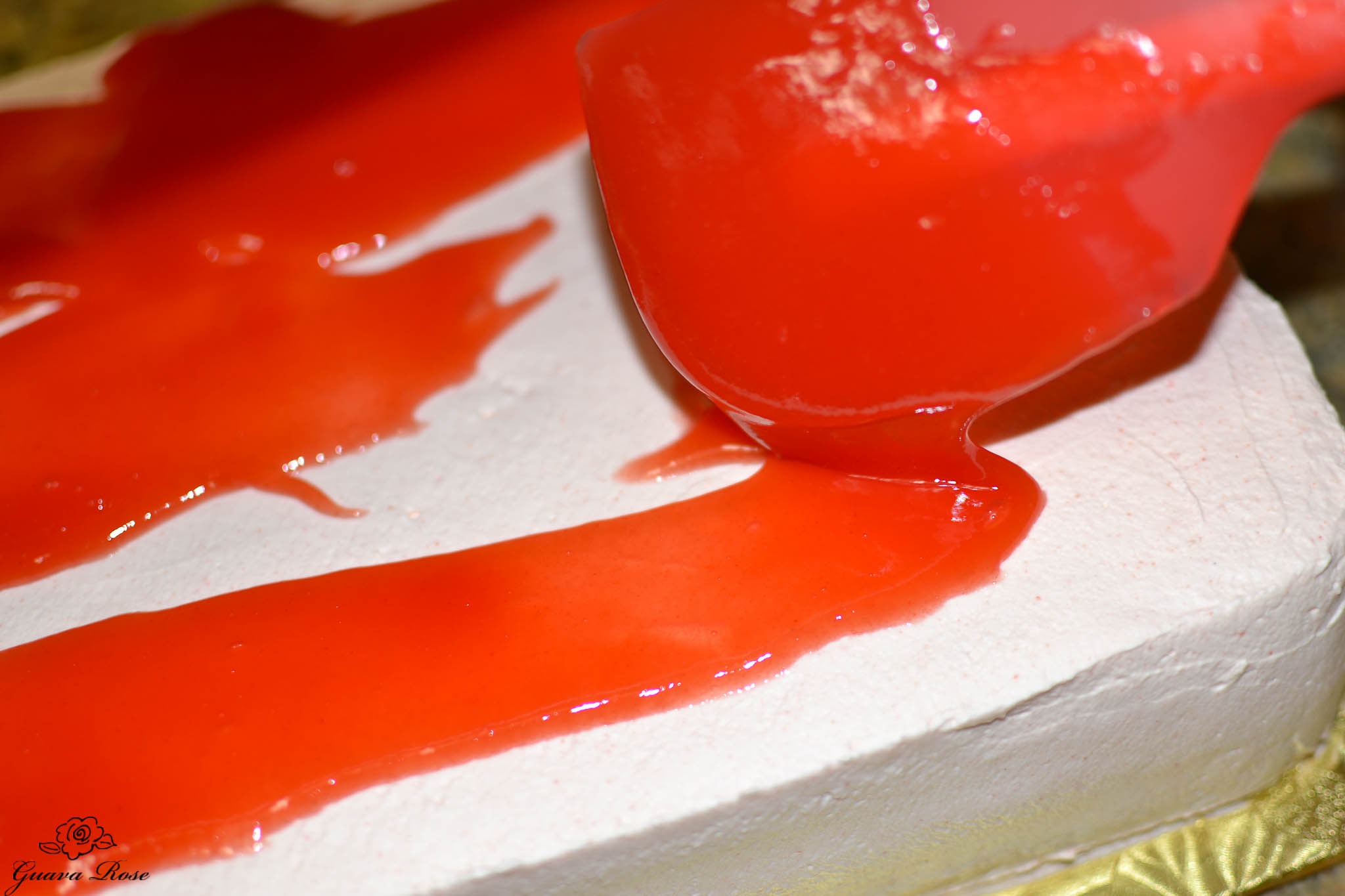 Streaming guava glaze over frosted cake, close up
